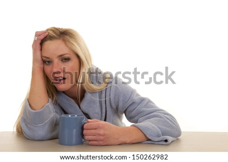 A woman in a blue robe with a cup looks tired
