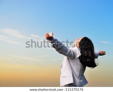 A woman in a business suit with their hands raised . On the background of the picturesque sky