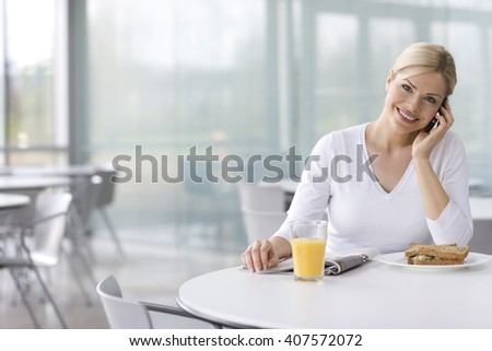 A woman in a cafe or office canteen, talking on a mobile phone - stock photo