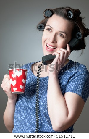 A woman in a domestic role happily talking on the phone at home. - stock photo