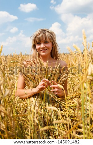 A woman in a dress made ??of straw in a wheat field