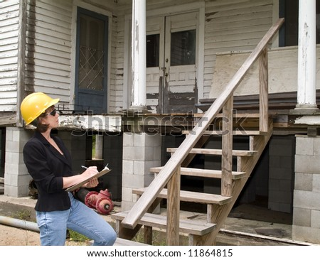 A woman in a hard hat, holding a clipboard, standing in front of an old house. - stock photo