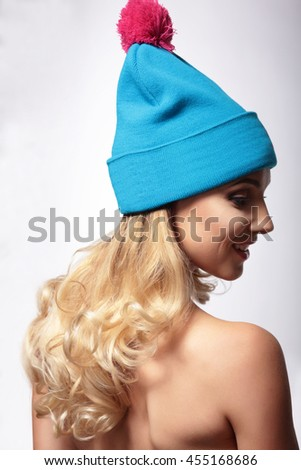 A woman in a knitted hat, stands back and looks down. - stock photo