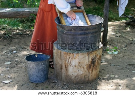 A woman in a long red skirt is washing clothes on a washboard and bucket set up by a stream.  Motion blur on hand scrubbing cloth on the board. - stock photo