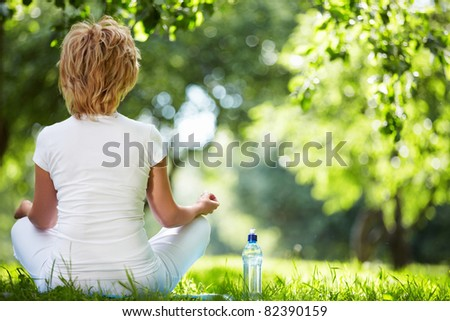 A woman in a park in the lotus position