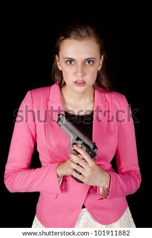 A woman in a pink jacket is holding a gun and looks very serious. - stock photo