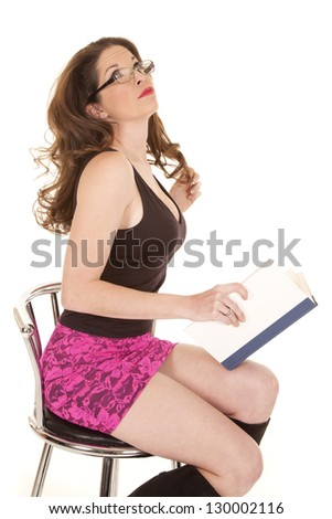 A woman in a pink skirt is reading a book. - stock photo
