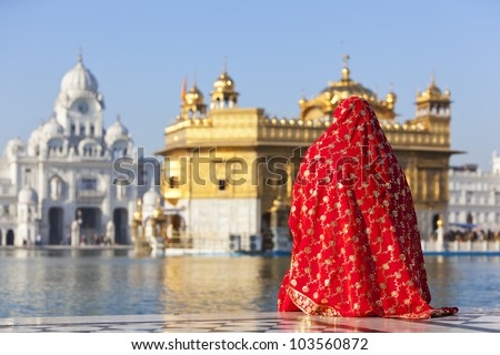 A woman in a red saree sat opposite the Golden Temple in Amritsar - India - stock photo