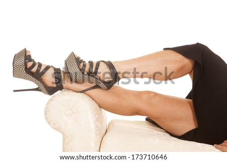 A woman in a skirt laying on a couch showing legs. - stock photo