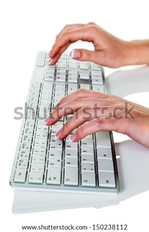 a woman in an office working on a computer keyboard - stock photo