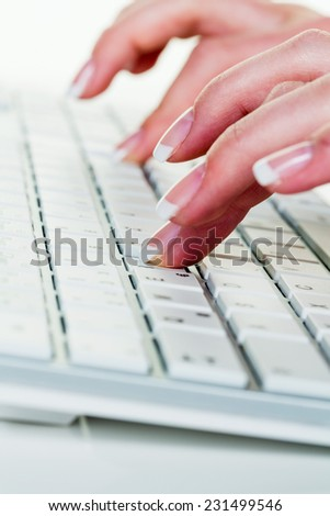 a woman in an office working on the keyboard of a computer - stock photo