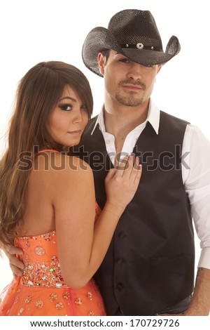 A woman in an orange dress is standing with cowboy. - stock photo