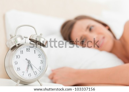 A woman in bed awake with her alarm clock on the desk beside her.