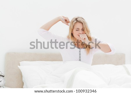 A woman in bed, leaning upright one arm stretching out and one hand covering her mouth as she yawns. - stock photo