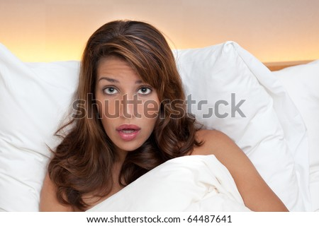 A woman in bed looks shocked or surprised