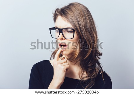 A woman in glasses, teeth hurt finger in mouth - stock photo