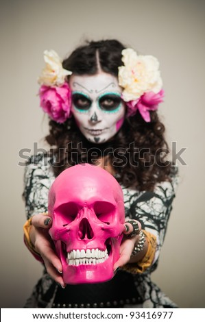 A woman in Halloween costume and skull makeup holding flowers - stock photo