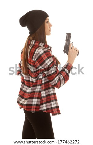 A woman in her beanie wearing her plaid shirt holding on to her gun. - stock photo