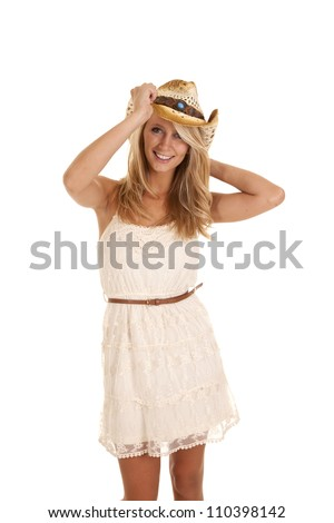 A woman in her beautiful lace dress holding on to her cowgirl hat with a smile on her face. - stock photo