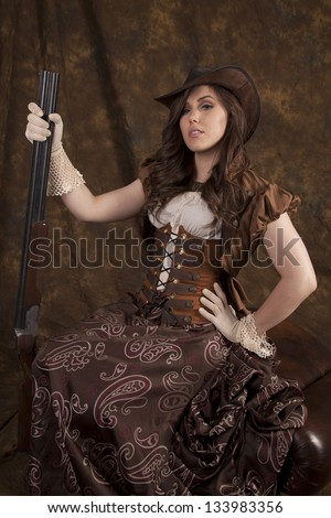 A woman in her beautiful western dress and corset holding on to her shot gun being a real cowgirl. - stock photo