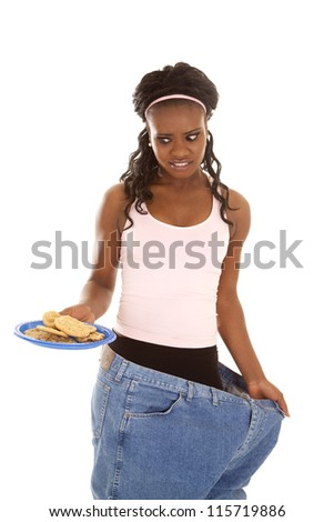 a woman in her big pants looking down at a plate of cookies with a funny expression. - stock photo