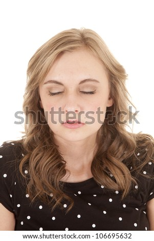 A woman in her black and white polka dot top with her eyes closed trying to remain calm - stock photo