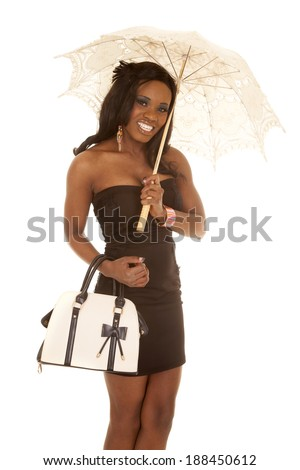A woman in her black dress holding on to the umbrella and her purse.