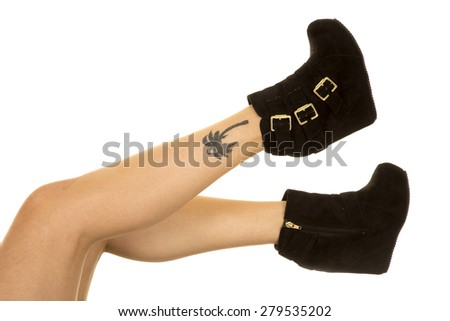 A woman in her black shoes, with a tattoo on her ankle. - stock photo