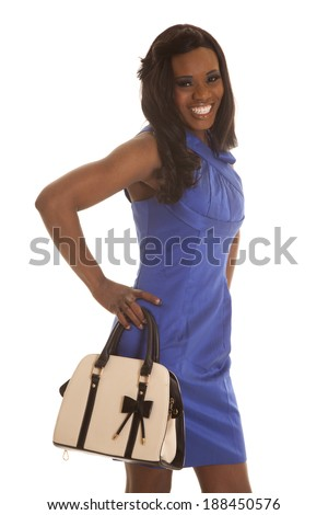 A woman in her blue dress smiling holding on to her purse. - stock photo