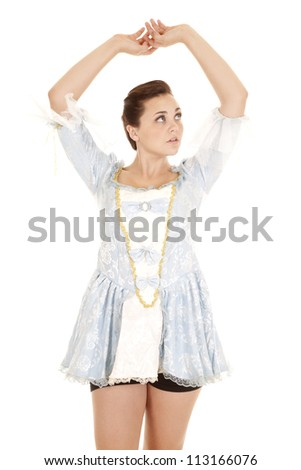 A woman in her blue dress with her arms up and a peaceful expression on her face. - stock photo