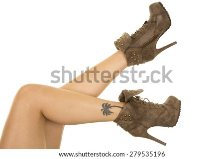 a woman in her brown shoes, with her tattoo showing. - stock photo