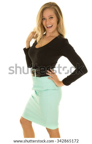 a woman in her business clothing, with a big smile on her face, playing with her hair. - stock photo