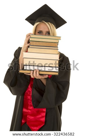 a woman in her cap and gown peeking over a stack of books. - stock photo