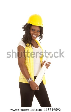 a woman in her construction clothes with hard hat and her blue prints with a smile on her face. - stock photo
