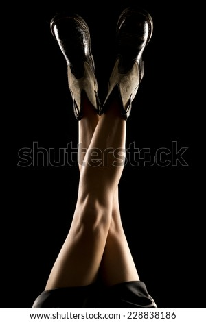 A woman in her cowboy boots with them up in the air. - stock photo