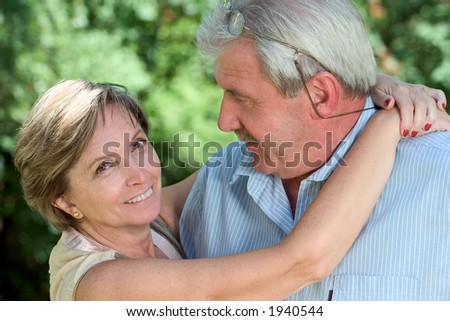 A woman in her fifties hugging her man and looking into the camera - stock photo