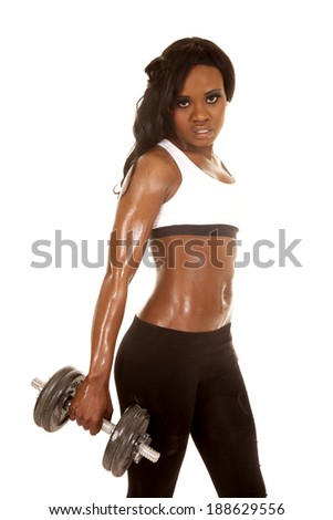 A woman in her fitness clothing holding on to a weight - stock photo