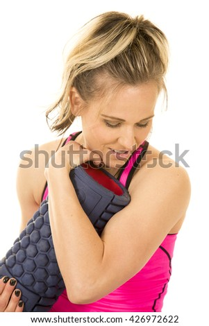 A woman in her fitness clothing hugging her roller. - stock photo