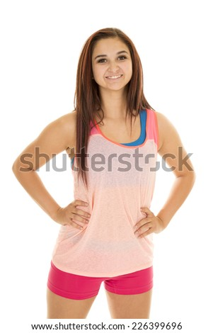 A woman in her fitness clothing with her hands on her hips. - stock photo