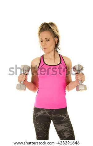A woman in her fitness gear working out with dumbbells. - stock photo