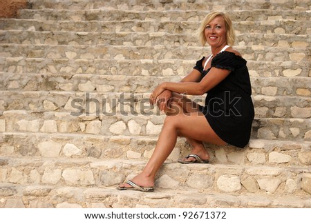 A woman in her forties sits on the staircase for a casual portrait.