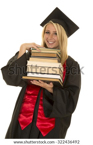 a woman in her graduation gown holding on to a stack of books with a smile.