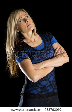 a woman in her lace top looking up with her arms folded. - stock photo