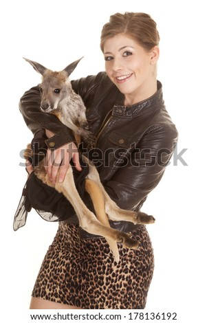 a woman in her leather jacket holding on to her pet kangaroo smiling. - stock photo