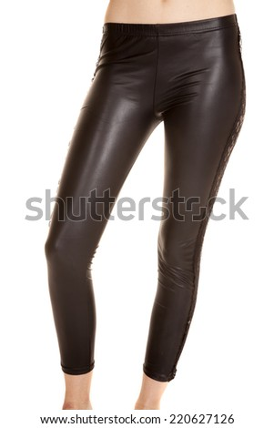 A woman in her leather leggings standing forward. - stock photo