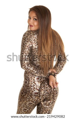 A woman in her leopard print costume holding on to her tail. - stock photo