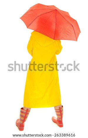 A woman in her long yellow rain coat and boots, with her back to the camera. - stock photo