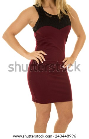 A woman in her maroon dress with her hands on her hips.