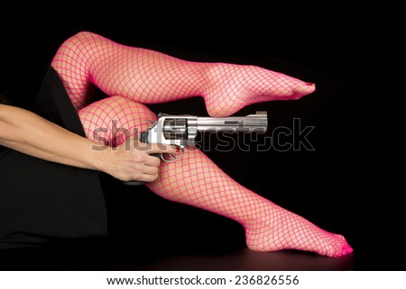 A woman in her pink fishnets holding onto a pistol. - stock photo