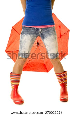 a woman in her rain boots with an umbrella behind her. - stock photo